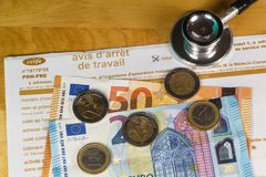 Medical work stop notice, black stethoscope and money. Medical work stop notice from france, black stethoscope, euros banknotes and coins stock image