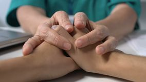 Medical worker comforting patient touching hands on table bad diagnosis, disease