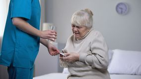 Medical worker giving pills elderly lady suffering from heart pain, treatment. Stock footage stock footage