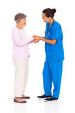 Medical worker greeting senior Royalty Free Stock Images