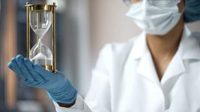 Medical worker holding sand hourglass on palm, terminal disease, life expiring. Stock photo royalty free stock images