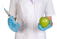 Medical worker holding a syringe injection and green apples Royalty Free Stock Photos