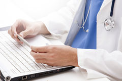 Medical worker with laptop. Medical worker in white lab coat and blue scrubs with stethoscope using laptop computer stock images