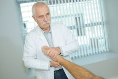 Medical worker manipulating patient`s foot. Medical Royalty Free Stock Images