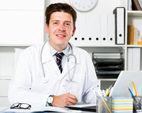 Medical worker in medical Center. Portrait of happy young medical worker in medical Center sitting at the table Royalty Free Stock Images