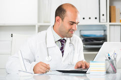 Medical worker in medical Center sitting at the table. Portrait of young medical worker in medical Center sitting at the table Stock Photo
