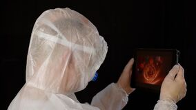 Medical worker in protective suit using tablet for blood tests in a science lab. Bioengineer looking blood movement in