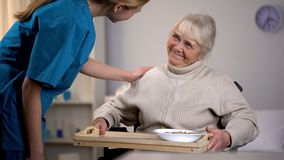 Medical worker taking care of aged female patient, gently care in nursing home royalty free stock image