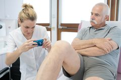 Medical worker taking photograph patient`s leg royalty free stock photography