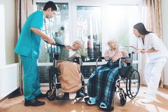 Medical workers argue with an elderly couple in a nursing home. They are very emotional. The elderly are very frightened. They are sitting in a wheelchair Royalty Free Stock Images
