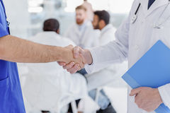 Medical workers greeting each other by handshake Royalty Free Stock Photo