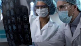 Medical workers looking at human brain MRI, discussing result to set diagnosis royalty free stock images