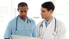 Medical workers looking over file on clipboard. At the hospital stock footage