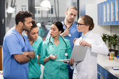Medical workers using laptop during discussion in lab. Group of medical workers using laptop during discussion in lab royalty free stock photography