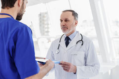 Medical working giving papers to general practitioner Royalty Free Stock Image