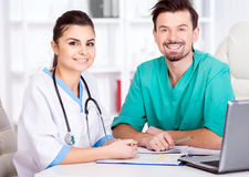 Medical. The young doctor and his assistant in a medical office at work stock photos