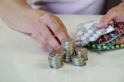 Medicals in hand. Hand with coins of money and blisters with pills Royalty Free Stock Photo