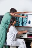 Medicals Technicians Working At Clinic. Male medical technician pointing at MRI x-ray while female jotting down notes on paper Royalty Free Stock Images