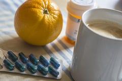 Medicamenta??o durante o caf? da manh?, c?psulas ao lado de uma laranja imagens de stock