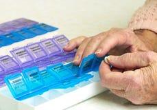 Medicamentos de venta com receita no organizador com mãos idosas Imagem de Stock Royalty Free