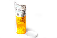 Medicamentos de venta con receta en un envase con cientos billetes de dólar fotografía de archivo libre de regalías