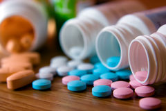 Medicaments. Closeup pink, white, blue and orange vitamins with bottles Stock Photos