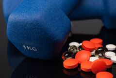 Medicaments. Colorful tablets or pills and blue dumbbells on black reflect background Stock Images