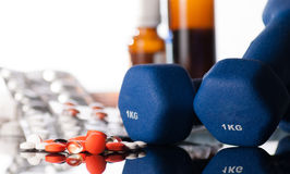 Medicaments. Colorful tablets or pills and blue dumbbells on reflect background Royalty Free Stock Images