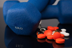 Medicaments. Colorful tablets or pills and blue dumbbells on reflect background Royalty Free Stock Photo