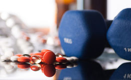 Medicaments. Colorful tablets or pills and blue dumbbells on reflect background Royalty Free Stock Photos