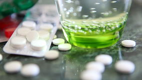 Medicaments and glass of water on green table. Sickness, flu concept