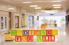 Medicare for All message built from wooden blocks. Medicare for All political policy for health insurance in wooden blocks against hospital background stock photography