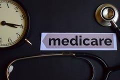 Medicare auf dem Druckpapier mit Gesundheitswesen-Konzept-Inspiration Wecker, schwarzes Stethoskop stockfotografie