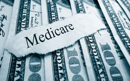 Medicare bills. Medicare paper headline on hundred dollar bills royalty free stock images