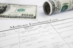 Medicare enroll. Closeup of a Medicare enrollment form with money Stock Photography