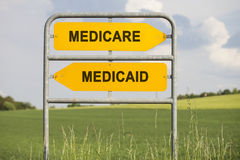 Medicare or  medicaid. Two yellow direction signs with arrows and the words medicare and medicaid, political and social concept for us health care Royalty Free Stock Images