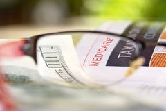 Medicare. Paper headline through reading glasses with hundred dollar bills stock photos
