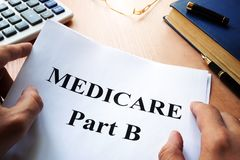 Medicare Part B on a desk. Medicare Part B and pen on a desk stock image