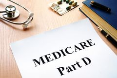Medicare Part D on a table. Medicare Part D policy and stethoscope on a hospital table stock images