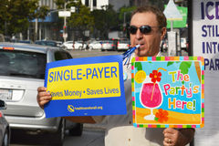 Medicare Rally. Los Angeles, CA - July 30, 2014: A demonstrator blows a noisemaker and holds two signs, one advocating single payer health insurance and the Royalty Free Stock Photo