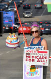 Medicare Rally. Los Angeles, CA - July 30, 2014: A demonstrator carrying a birthday cake on a pole and a sign advocating Medicare For All celebrates the 49th Stock Images