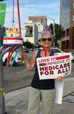 Medicare Rally. Los Angeles, CA, USA - July 30, 2014: A demonstrator carrying a birthday cake on a pole and a sign advocating Medicare For All celebrates the Stock Image