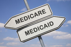 Medicare vs. medicaid. Two white direction signs with arrows and the words medicare and medicaid, political and social concept for us health care Stock Photos