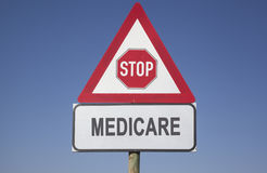 Medicare warning. Red warning triangle with a stop sign and the word medicare, political and social concept for us health care Royalty Free Stock Image