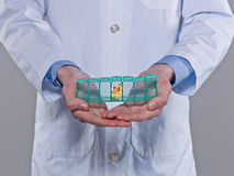 Medication-9. Person in labcoat holding a pillbox with colorful capsules Stock Images