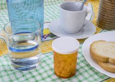 Medication during breakfast, capsules next to a glass of water, conceptual image stock photography