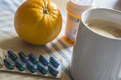 Medication during breakfast, capsules next to a orange stock images