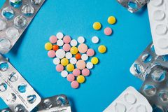 Medication tablets on color background. Concept of health, treatment, choice, healthy lifestyle. Medication colorful round tablets in form of diffusion heart on royalty free stock images