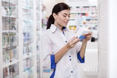 Reflective female pharmacist supervising production. Medication control. Smart female pharmacist gazing down while carrying medication stock photo