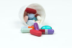 Medication Cup. Different colorful medications spill from paper medication cup Royalty Free Stock Photo